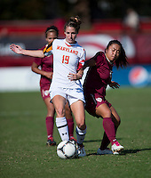 Becky Kaplan (19) of Maryland passes the ball away from Hikaru Murakami (18) of Florida State during the game at Ludwing Field in College Park, MD.  Florida State defeated Maryland, 1-0.