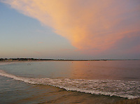 A red cloud at sunset lights up the sky at Narragansett Beach