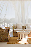 Long white curtains shield the outdoor seating area from the Adriatic sun
