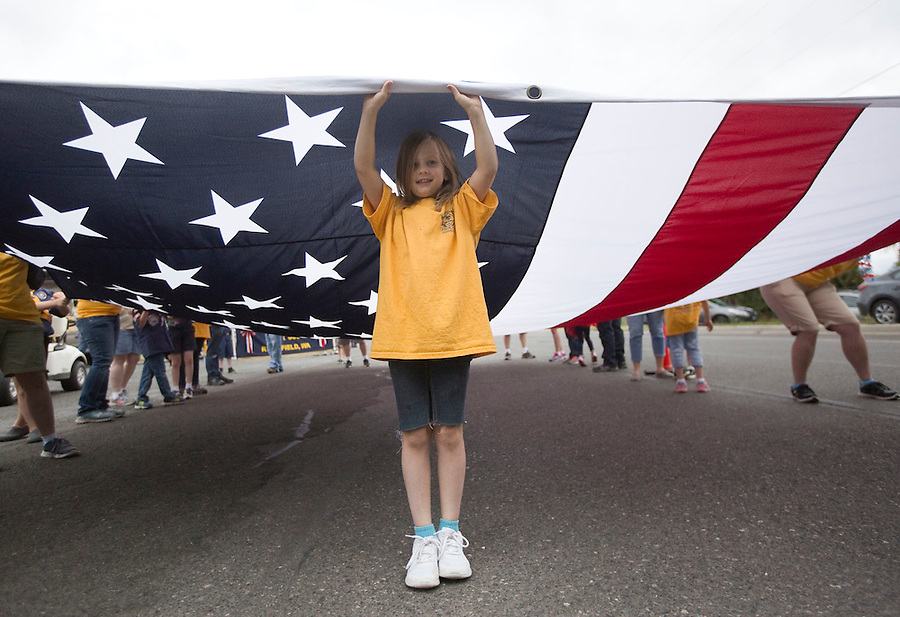 Paige Rippee, 7, helps carry a giant flag with the cub scouts pack 310, as they take part in the Fourth of July Parade through the town of Ridgefield Monday July 4, 2016. (Photo by Natalie Behring/ for the The Columbian)
