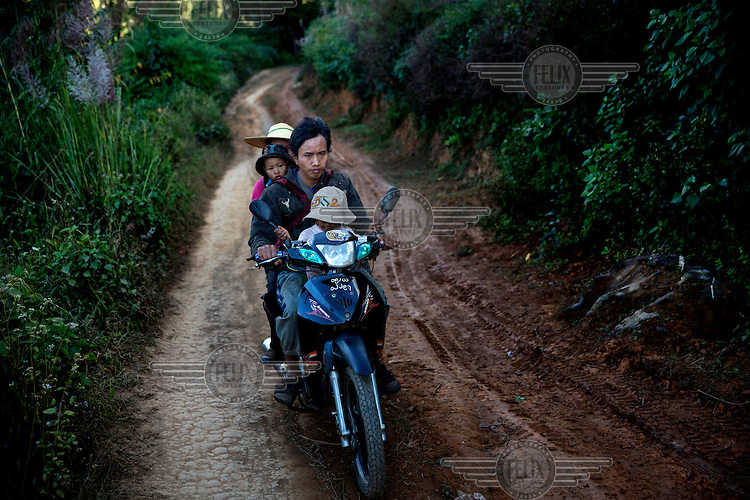 Villagers ride a motorbike through new roads built by United Nations Office on Drugs and Crime (UNODC) to help then access markets and move away from poppy production in Bang Laem Village in a Shan State Army - South controlled area of Shan State.