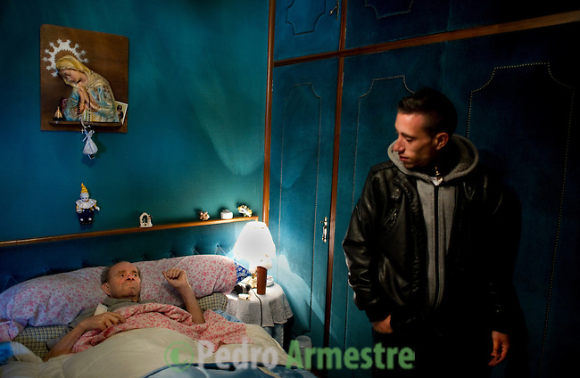 SPAIN, Madrid : Spanish Vicente Torres, 73, lies in his bed next to his grandson Jonathan Torres (R) in his appartment in Madrid on April 18, 2012. Torres, who is severy ill and underwent a recent heart surgery, faces an eviction from his house. Eviction procedures in Spanish courts for unpaid mortgages and rent hit a record of 58,241 in 2011, a 21.2 percent rise over the previous year. Evictions have soared in Spain since the collapse of a property bubble in 2008 that triggered the country's economic crisis. (c) Pedro ARMESTRE