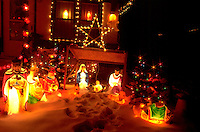 Outdoor lighted crèche scene of kings bearing gifts in snowy yard of house. St Paul Minnesota USA