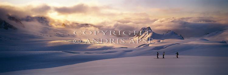 Three skiers. Sun breaking through cloud. Upper Fox Glacier. Westland National Park. New Zealand.