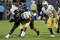 17 September 2011:  FIU linebacker Jordan Hunt (25), with defensive end Tourek Williams (97) looking on, brings down UCF quarterback Jeff Godfrey (2) in the second half as the FIU Golden Panthers defeated the University of Central Florida Golden Knights, 17-10, at FIU Stadium in Miami, Florida.