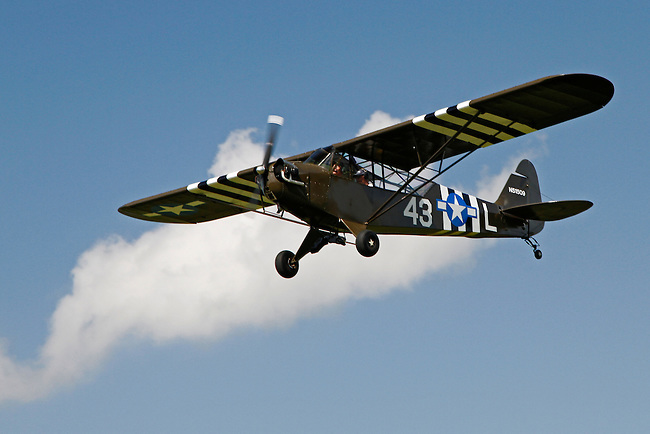A brown 1943 Piper J3C-65 with white detailing flies past a fluffly cloud in a blue sky at the 2010 Wings 'n' Wheels Showcase.