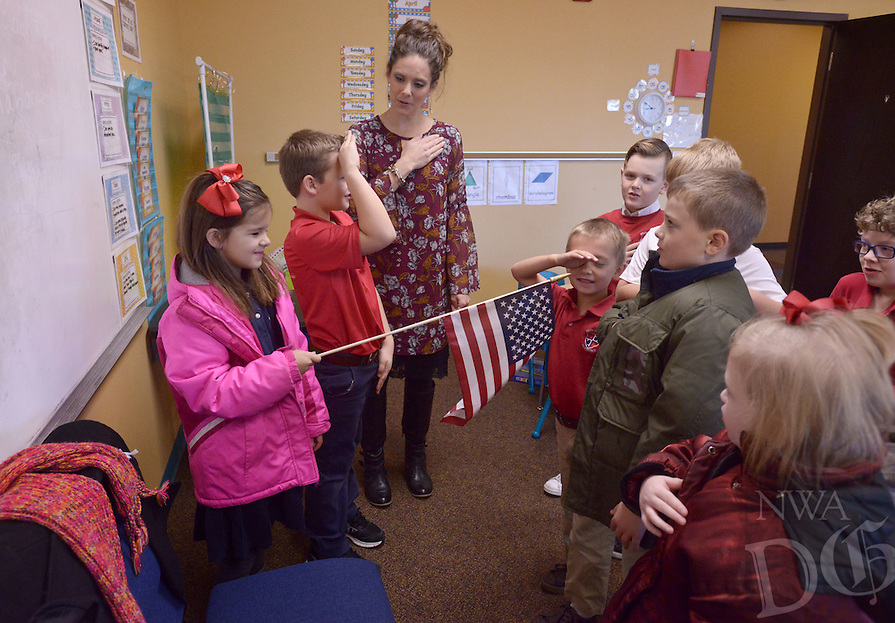 NWA Democrat-Gazette/BEN GOFF @NWABENGOFF<br /> Olivia Hamm, 6, holds the flag as teacher Nikki Looney leads her 1st grade class in reciting the Pledge of Allegiance on Monday Dec. 19, 2016 at Providence Academy's grammar school campus at Immanuel Baptist Church in Rogers.
