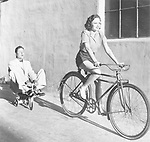 Woman on a bicycle pulling a grown man on a toy tricycle