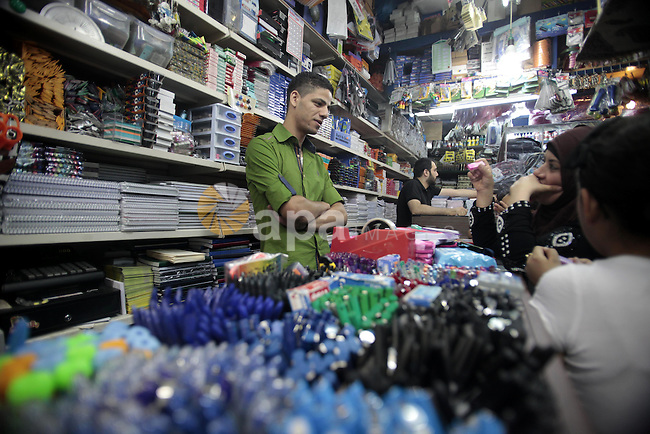 Palestinians shop during preperation for the new school year at a market in Jerusalem on Aug 22, 2013. Palestinian Ministry of Education announced the 25 August is the first day of new school year in the West Bank and Gaza Strip. Photo by Saeed Qaq