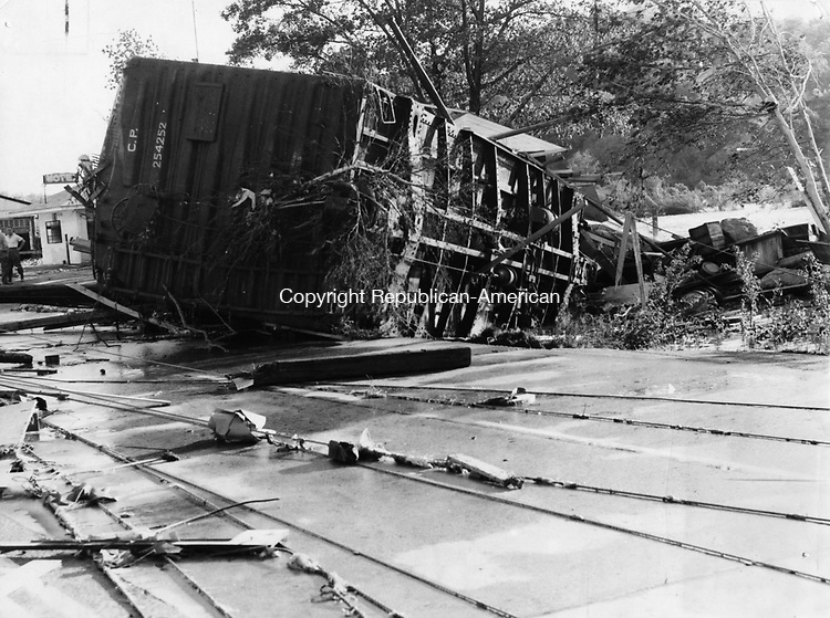 a steel boxcar tossed across the pavement by the flood lies on its side mostly on South Main Street in Waterbury. 22 August 1955.