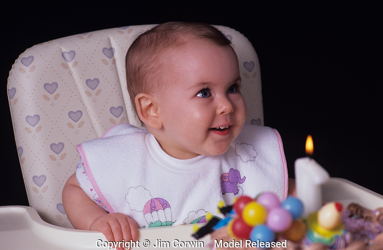 Girl,(12 months old) first birthday looking at cake and one lit candle, sitting in a highchair with surprised, happy look on face