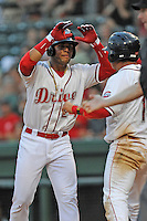 Second baseman Yoan Moncada (24) of the Greenville Drive slaps hands with Francisco Tellez (19) after both scored in a game against the Lexington Legends on Monday, May 18, 2015, at Fluor Field at the West End in Greenville, South Carolina. Moncada, a 19-year-old prospect from Cuba, made his professional debut tonight in the Red Sox organization. (Tom Priddy/Four Seam Images)