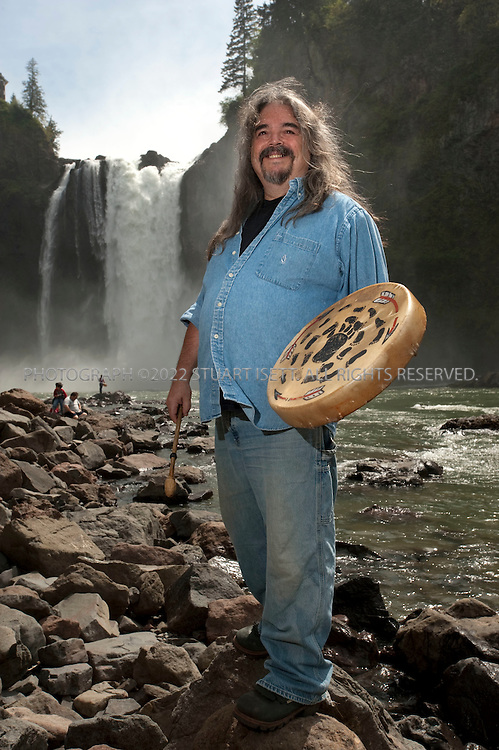 """5/10/2009--Snoqualmie, WA, USA..Ray Mullen, the Snoqualmie tribe's """"drum bearer"""" and one of nine members of the democratically elected Tribal Council that runs the tribe, poses at Snoqualmie Falls, what he calls the tribe's 'church'. As drum bearer, Mullen is responsible for learning traditional Snoqualmie songs and sharing them at tribal ceremonies whenever he is called to serve. ..The Snoqualmie Falls is a 268 ft (82 m) waterfall on the Snoqualmie River between Snoqualmie and Fall City, Washington, USA. For the Snoqualmie People, who have lived for centuries in the Snoqualmie Valley in western Washington, Snoqualmie Falls is central to their culture, beliefs, and spirituality. A traditional burial site, to the Snoqualmie, the falls are """"the place where First Woman and First Man were created by Moon the Transformer"""" and """"where prayers were carried up to the Creator by great mists that rise from the powerful flow."""" The mists rising from the base of the waterfall are said to serve to connect Heaven and Earth...©2009 Stuart Isett. All rights reserved."""