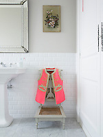 A bright pink waistcoat hangs on the back of an antique chair in the bathroom
