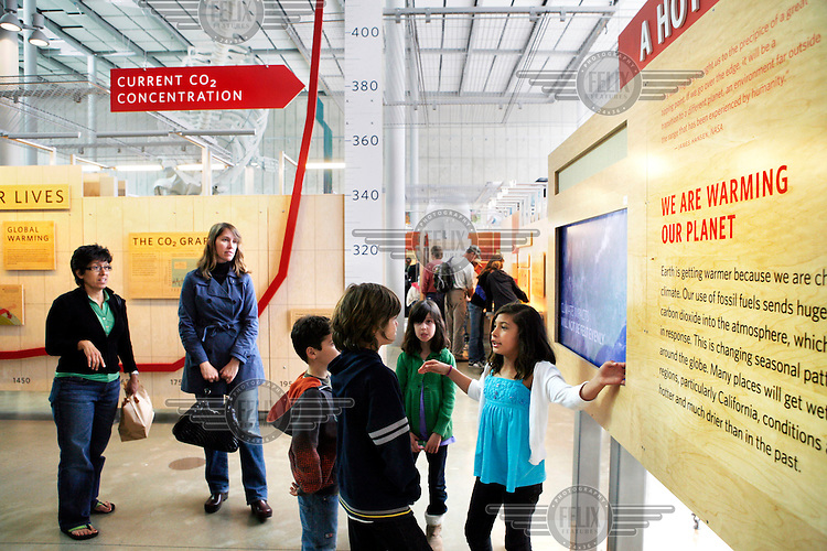 """A young boy looks at a CO2 graph showing the current carbon dioxide concentration and a board saying """"We are warming our plant"""", at an exhibition about climate change and global warming at the California Academy of Science, San Francisco."""