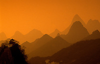 Guilin, China.  Sunset over the area's extraordinary landscape. Clifftop temple in the foreground.