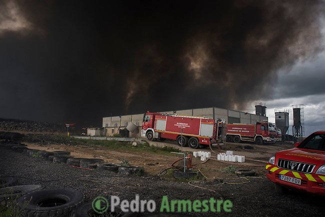 Clouds of dark smoke cover the sky as a fire truck works among piles of tyres in an uncontrolled dump near the town of Sesena, after a fire broke out early on May 13, 2016. A huge waste ground near Madrid where millions of tyres have been dumped was on fire today, releasing a thick black cloud of toxic fumes that officials worry could harm residents nearby.  © Pedro ARMESTRE