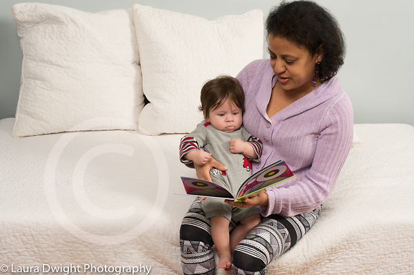 4 month old baby boy held by mother who is reading a book to him, older mother first child in her 40s