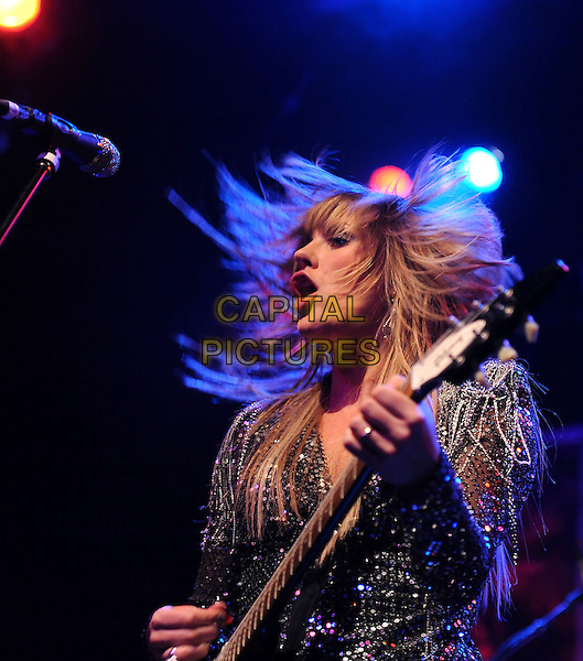 GRACE POTTER of Grace Potter and The Nocturnals .performs live at The El Rey Theatre in Los Angeles, California, USA, .February 4th 2011..music concert gig on stage half length beaded  mini dress black silver  microphone   singing playing guitar side                                                        mouth open hair funny profile .CAP/RKE/DVS.©DVS/RockinExposures/Capital Pictures.