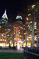 The holiday lights of Rittenhouse Square blur into the skyline of Philadelphia.
