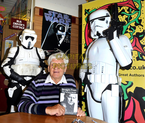 Dave Prowse MBE signing his new book 'Straight From The Forces's Mouth' at Coles Books, Bicester, Oxford, England, June 23rd 2012..half length striped purple jumper white shirt collar smiling sitting Star Wars storm troopers.CAP/ROS.©Steve Ross/Capital Pictures.