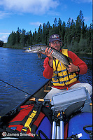 Man holding northern pike after fishing