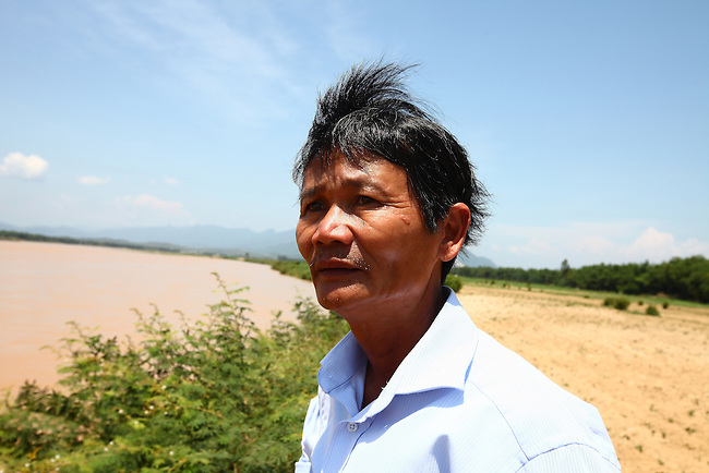"Nguyen Tan Hoa, 55, stands on the bank of the Vu Gia River across from the spot where Sgt. Michael Frank Flynn was killed in April, 1965 outside the village of Tam Hoa, Vietnam. Flynn was the team leader for Charlie 2-2-4 under the Combined Action Program, which sent small units of Marines into villages in South Vietnam to train local militia and keep Viet Cong guerrillas out. As a boy, Nguyen spent much of his free time hanging out with the Marines, who adopted him into the unit. It was the most profound experience of his life, and he still refers to himself proudly as a Marine. ""When the Americans left in '75, I really felt like I was the last G.I. in Vietnam,"" he says. May 12, 2012."