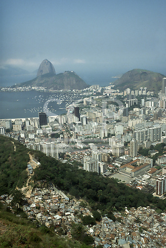 Rio de Janeiro, Brazil. Dona Marta shanty town 'favela' in the foreground with the Santo Ignacio school, high-rise buildings of Botafogo and the Sugar Loaf behind; view looking west.