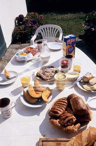 Pendruc, Britanny, France. Breakfast table with pastries, bread, croissants, pain au chocolat, melon, cheese, orange juice.