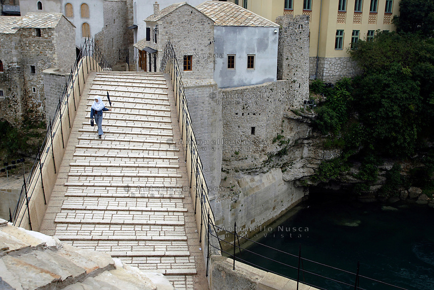 Una giovane musulmana attraversa iil vecchio ponte di Mostar dopo la sua riapertura avvenuta a 11 anni dalla sua distruzione durante la sanguinosa guerra.<br /> A young muslim girl crosses the bridge. The 16th-Century bridge was blown up during the bitter fighting in the Bosnian war between the city's Muslims and Croats in 1993. Its reopeningafter 11 yers, is being seen as symbolic of the healing of divisions between Muslims and Croats.