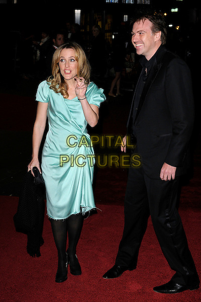 "GILLIAN ANDERSON & MARK GRIFFITHS .attending The 54th BFI London Film Festival Opening Night Gala & European Premiere of ""Never Let Me Go"" Odeon Leicester Square, London, England, UK,.13th October 2010..full length couple green knotted draped ruched dress turquoise silk satin black suit frayed hem hand gesture funny .CAP/CAN.©Can Nguyen/Capital Pictures."