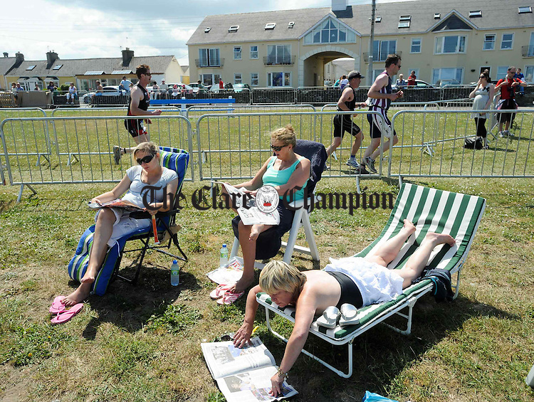 Jean Carbury, Christina Carbury and Sinead Carbury were a bit pre-occupied with their reading during the  Hell Of The West Triathlon at Kilkee. Photograph by John Kelly.