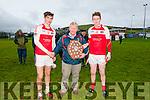 Muiris Ó Fiannachta (West Kerry Board) presenting the shield to the Daingean Uí Chúis Minor captains Liam Ó Brosnochain and Tomas Mac a-tSithaigh in Pairc an Aghasaigh, Dingle, on Saturday afternoon.