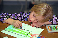 Girl age 7 coloring picture at Youth Express Christmas Party.  St Paul  Minnesota USA