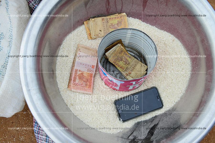 BURKINA FASO, Bobo Dioulasso, village Bama, women sell rice at the road, vessel with rice , CFA money and smartphone / Dorf Bama, Frauen beim Reisverkauf an der Strasse, CFA Geldscheine und Smartphone
