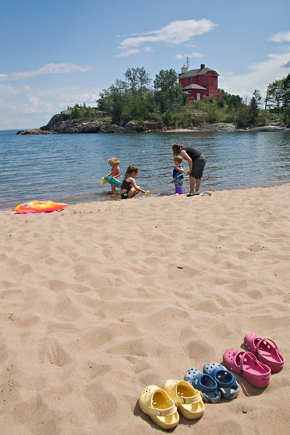 A family at the McCarty Cove beach on Lake Superior near the Marquette Lighthouse in Marquette Michigan.
