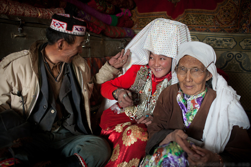 Mustafa Qol plays with his young wife. His mother stands nearby. Inside Mustafa Qol's house..At the camp of Tash Seri (Mustafa Qol's camp)...Trekking through the high altitude plateau of the Little Pamir mountains, where the Afghan Kyrgyz community live all year, on the borders of China, Tajikistan and Pakistan.