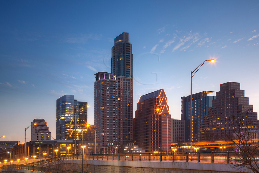 From the upper parking area that leads to the Hike and Bike Trails along Zilker Park and Lady Bird Lake, this image shows downtown Austin, Texas. The skyline rises over the First Street Bridge, seen here just a little before sunrise on a winter morning.