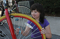 NWA Democrat-Gazette/FLIP PUTTHOFF<br /> Robbie Rheam (cq), 9, cleans spokes on repaired bicycles Saturday August 8 2015 at First Christian Church in Bentonville.