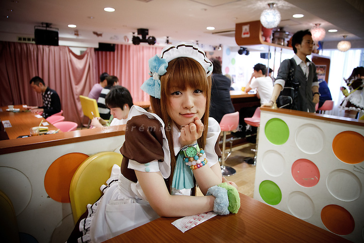 """Tokyo, May 2011 - A waitress posing at """"At Home"""" maid cafe in Akihabara. Male customers come in maid cafe to talk with girls dressed with maid clothes."""