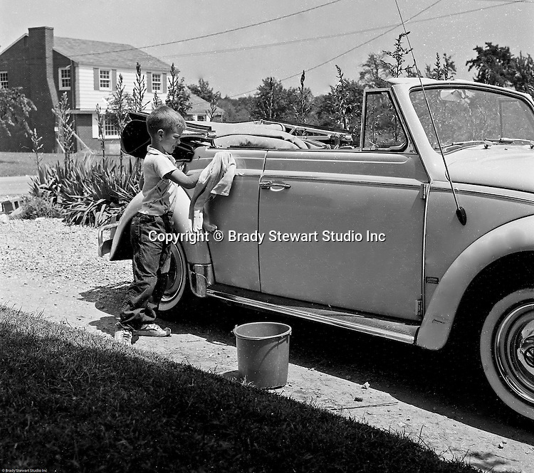Bethel Park PA:  View of Michael Stewart washing the Stewart's new Volkswagen Beetle convertible - 1959.