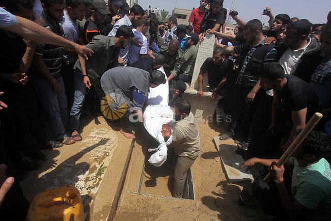Palestinians bury the body of Haitham Al-Mes-hal, who relatives said belonged to a militant Jihadist Salafi organisation, during his funeral at a cemetery in Gaza City April 30, 2013. Israel on Tuesday launched its first targeted attack on a militant in Gaza since a war in November, killing the Palestinian jihadist in an air strike that put further strain on a five-month-old ceasefire. Photo by Ashraf Amra