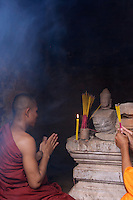 Buddhist Monk praying at a small temple in outskirts of Siem Reap, Cambodia