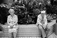 Switzerland. Canton Zürich. Winterthur. Two old people sit on a wall in a shopping center. The man smokes a cigar and wears a cap on the head. He smiles and holds a newspaper in his hands. The woman has a dress with flowers and holds tight her handbag on her legs. © 1990 Didier Ruef
