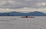 Alaska, Sea kayaker fishing, salmon jumping, Prince William Sound,