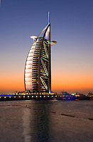 Dubai.  Evening view over marina at Jumeirah Beach Hotel  of Burj al Arab Hotel, architect W.S. Atkins, an icon of Dubai built in the shape of the sail of a dhow, stands on an island off Jumeirah Beach. .