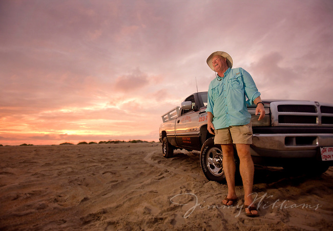 A fisherman scouts for spots to fish on the North Carolina coast, driving on the beach in his truck