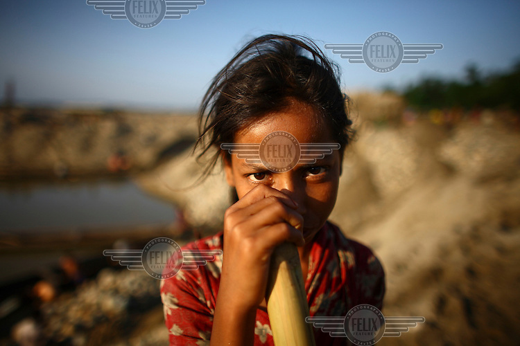 A child at Bhollar Ghat. At least 10,000 people, including 2,500 women and over 1,000 children, are engaged in stone and sand collection from the Bhollar Ghat on the banks of the Piyain river. Building materials such as stone and sand, and the cement which is made from it, are in short supply in Bangladesh, and commands a high price from building contractors. The average income is around 150 taka (less than 2 USD) a day.
