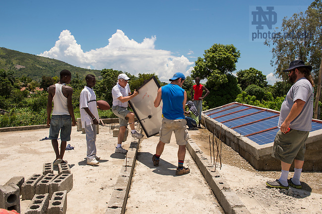 Aug. 11, 2015; Bill Jordan and son Stephen (center) work with a crew on the solar panel installation project at St. Gabriel School in Fontaine, Haiti. (Photo by Barbara Johnston/University of Notre Dame)