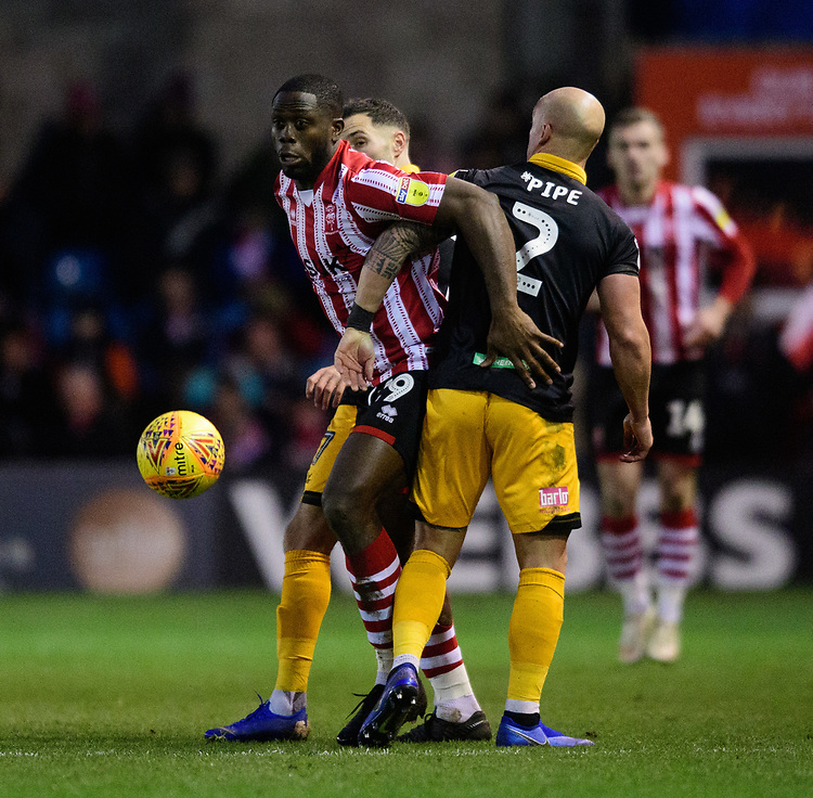 Lincoln City's John Akinde vies for possession with Newport County's David Pipe<br /> <br /> Photographer Chris Vaughan/CameraSport<br /> <br /> The EFL Sky Bet League Two - Lincoln City v Newport County - Saturday 22nd December 201 - Sincil Bank - Lincoln<br /> <br /> World Copyright © 2018 CameraSport. All rights reserved. 43 Linden Ave. Countesthorpe. Leicester. England. LE8 5PG - Tel: +44 (0) 116 277 4147 - admin@camerasport.com - www.camerasport.com